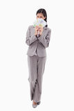 Businesswoman hiding face behind bank notes Royalty Free Stock Image