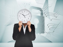 Businesswoman hiding face with clock Stock Images