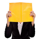Businesswoman hiding her face behind a book Royalty Free Stock Photography