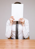 Businesswoman hiding her face behind documents Stock Image