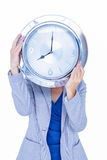 Businesswoman hiding her head with clock Stock Images