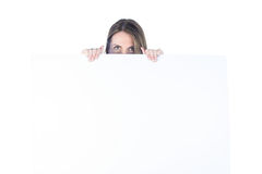Businesswoman hiding herself behind a blank sign Royalty Free Stock Photos
