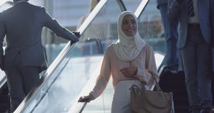 Businesswoman in hijab using escalator in a modern office 4k. Front view of Asian Businesswoman in hijab using escalator in a modern office. She is smiling and stock footage