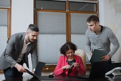 Businesswoman and his assistants secretaries in his office. The secretaries brought the boss documents to sign Royalty Free Stock Photo