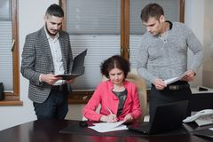 Businesswoman and his assistants secretaries in his office. The secretaries brought the boss documents to sign Stock Photo