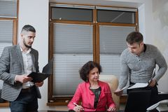 Businesswoman and his assistants secretaries in his office. The secretaries brought the boss documents to sign Royalty Free Stock Image