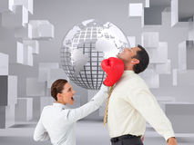 Businesswoman hitting a businessman with boxing gloves Stock Images