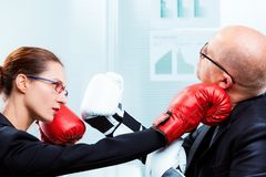Businesswoman hitting businessman`s face with a punch Royalty Free Stock Photo