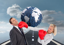 Businesswoman hitting colleague with her boxing gloves Royalty Free Stock Photos