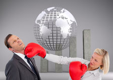 Businesswoman hitting colleague with her boxing gloves Stock Photos
