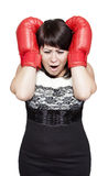 Businesswoman hitting herself with boxing gloves Stock Image