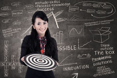 Businesswoman hold bull's eye in class Royalty Free Stock Images