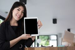 Businesswoman hold digital tablet at workplace. young woman show. S information in touchpad at office. female freelancer present data at cafe coffee shop Stock Image