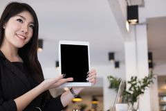 Businesswoman hold digital tablet at workplace. young woman show. S information in touchpad at office. female freelancer present data at cafe coffee shop Royalty Free Stock Image