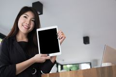 Businesswoman hold digital tablet at workplace. young woman show Stock Photos