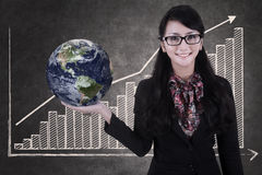 Businesswoman hold globe on growing bar chart chalkboard Stock Photo