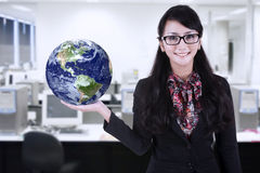 Businesswoman hold globe at office. Businesswoman is holding world globe at office Royalty Free Stock Photo