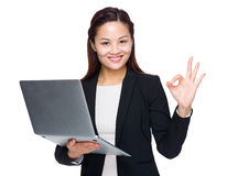 Businesswoman hold laptop computer with ok sign Royalty Free Stock Photo