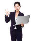 Businesswoman hold with laptop and ok sign Stock Photo