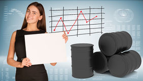Businesswoman hold paper sheet. Black oil barrels Royalty Free Stock Photo