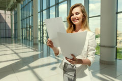 Businesswoman hold some documents. Against a big window. Image with split toned techniques Stock Image