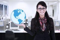 Businesswoman hold world globe at office. Businesswoman is holding blue world global at office Stock Photo