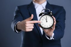 Businesswoman holding alarm clock on color background royalty free stock image