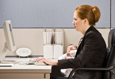Businesswoman holding baby at desk Stock Photography