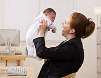 Businesswoman holding baby at desk Royalty Free Stock Photography