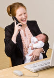 Businesswoman holding baby at desk Royalty Free Stock Photos