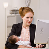 Businesswoman holding baby at desk Stock Images
