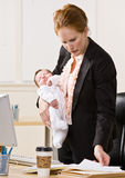 Businesswoman holding baby at desk Stock Image