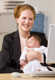 Businesswoman holding baby at desk Stock Photos