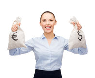 Businesswoman holding bags with dollar and euro Royalty Free Stock Photo