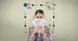 Businesswoman holding banknotes against signs on wall. Digital composite of Businesswoman holding banknotes against signs on wall Royalty Free Stock Photos