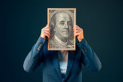 Businesswoman holding Benjamin Franklin 100 USA dollar portrait. In front of her face royalty free stock photo