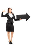 Businesswoman holding a big black arrow Royalty Free Stock Photography
