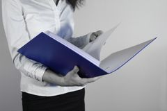 Businesswoman Holding a Binder. In blue royalty free stock photos