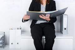Businesswoman Holding Binder While Sitting On Counter Royalty Free Stock Photos