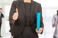 Businesswoman holding a binder. Businesswoman with thumbs up holding a binder Stock Images