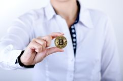 Businesswoman holding bitcoin isolated on a white background.Golden bitcoin coins in women`s hands. Virtual currency. Royalty Free Stock Photos