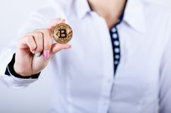 Businesswoman holding bitcoin isolated on a white background.Golden bitcoin coins in women`s hands. Virtual currency. Stock Photography