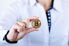 Businesswoman holding bitcoin isolated on a white background.Golden bitcoin coins in women`s hands. Virtual currency. Stock Image