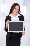Businesswoman holding blank chalkboard Royalty Free Stock Photography