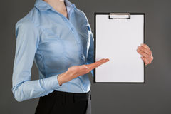 Businesswoman holding blank clipboard Stock Images