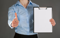Businesswoman holding blank clipboard and showing thumb up Stock Photography
