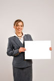 Businesswoman holding a blank page. Business woman holding a large blank card Stock Images