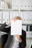 Businesswoman Holding Blank Paper In Front Of Face Royalty Free Stock Image