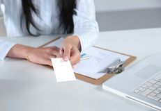 Businesswoman holding blank visit card ,sitting on the desk Stock Images