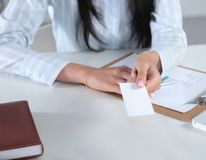 Businesswoman holding blank visit card ,sitting on the desk Royalty Free Stock Image